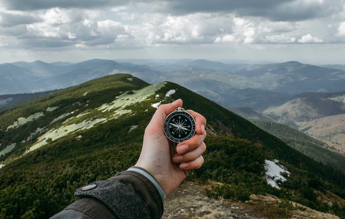 hand with compass looking below at mountains