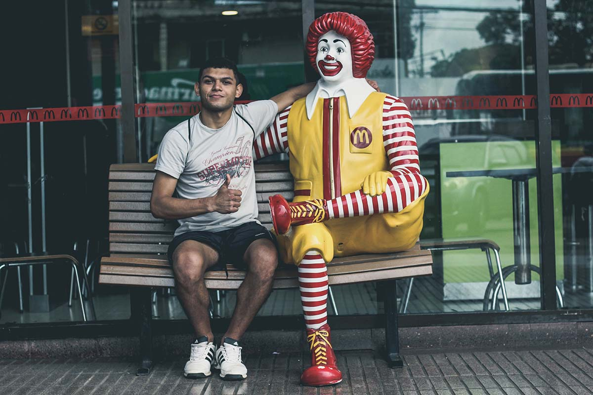 man sits next to Ronald McDonald on a seat