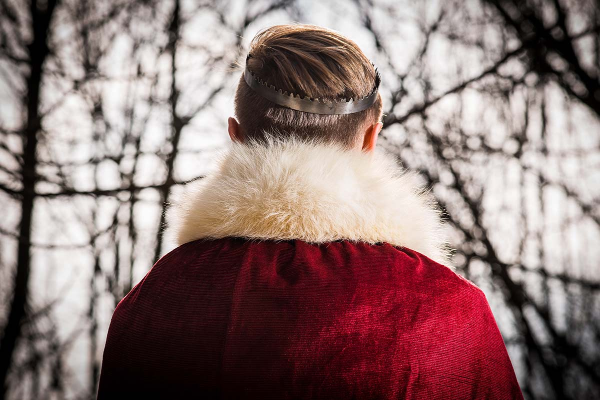 back of man with crown and red regal coat.